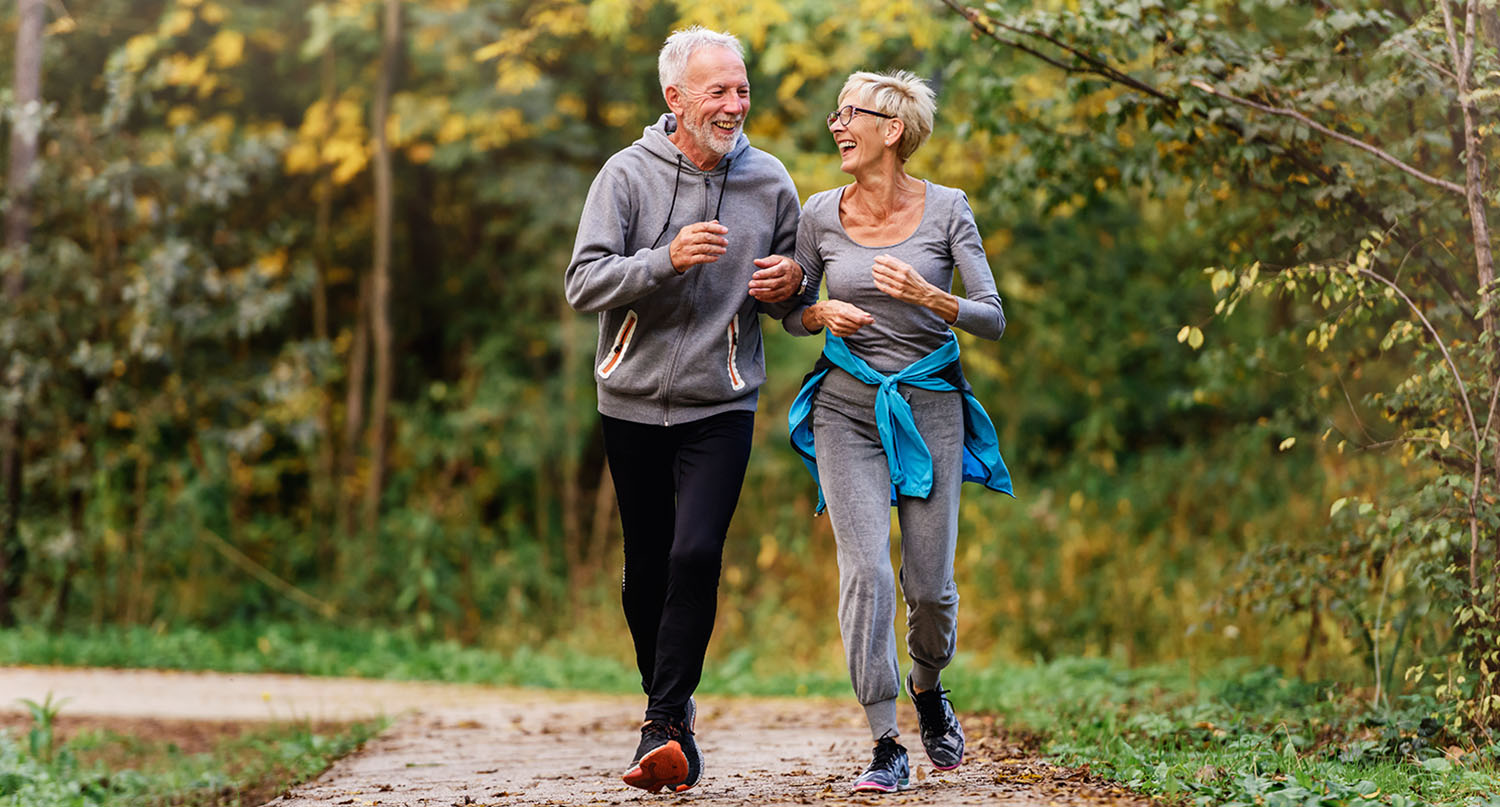 Cheerful active senior couple jogging in the park. Exercise toge